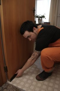 Worker putting on a door draught excluder in a home