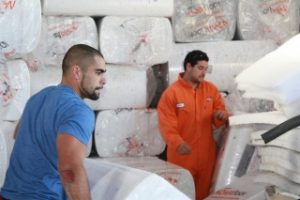 Two workers bringing insulation into an office building