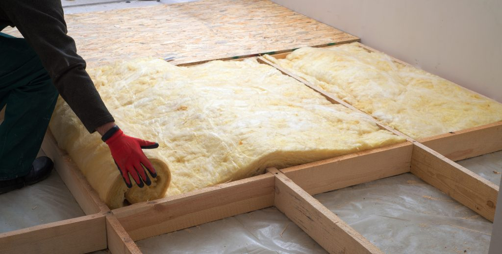 Worker laying down insulation in a home