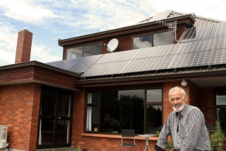 Michael proudly standing in front of his new solar panels on his home